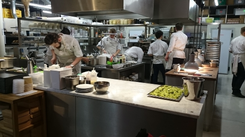 Male chefs work in kitchen with shiny appliances