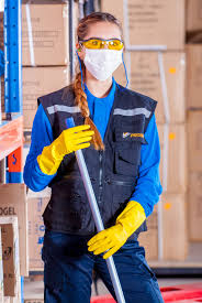 Woman in face mask and safety glasses stands in warehouse with mop