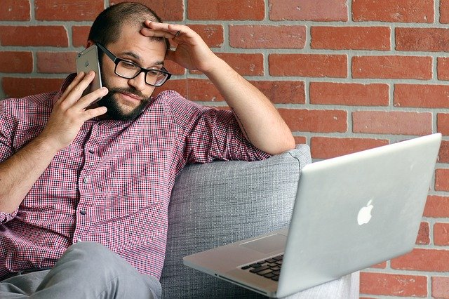 Stressed-looking worker stares gloomily at laptop while holding phone to his ear