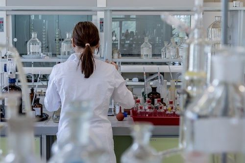 rear view of woman in lab coat and pony tail working in a laboratory