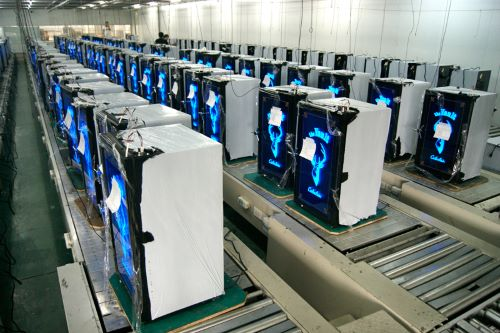 Assembly line of white refrigerators wait to be tested in factory